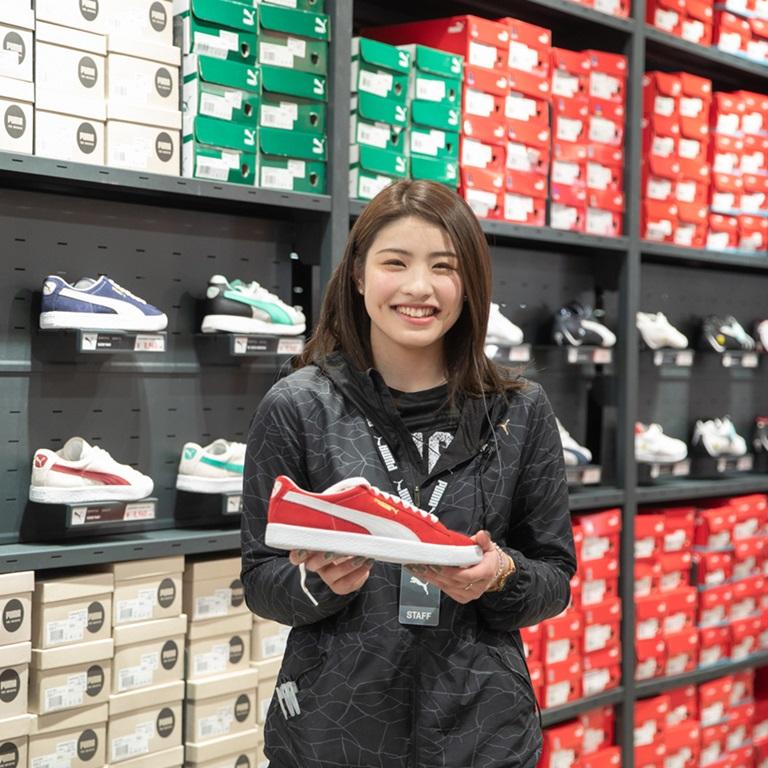 Lachende PUMA Mitarbeiterin zeigt einen roten PUMA Schuh